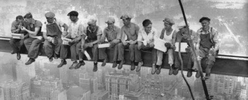 29 Sep 1932 --- Construction workers eat their lunches atop a steel beam 800 feet above ground, at the building site of the RCA Building in Rockefeller Center. --- Image by © Bettmann/CORBIS